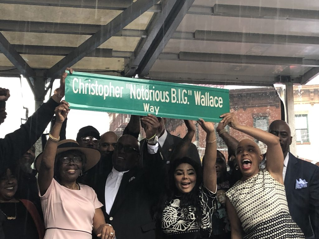 group of people hold the christopher wallace way street sign